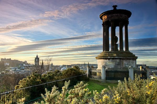 a photograph at sunset overlooking edinburg from a hill on which a moment stands