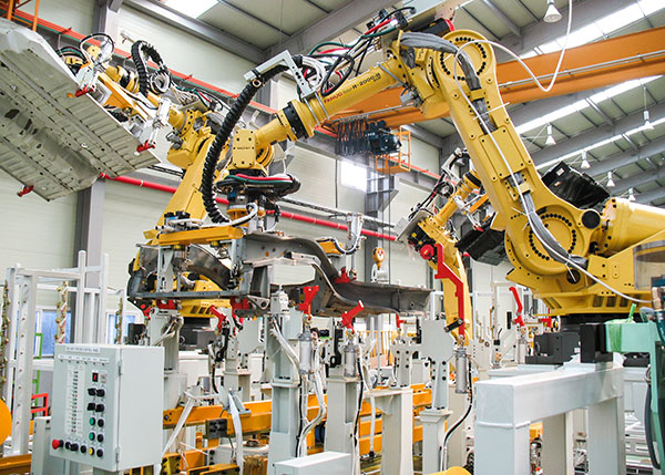 an industrial robot, looking like a very large arm, adjusts the placement of material in in a room