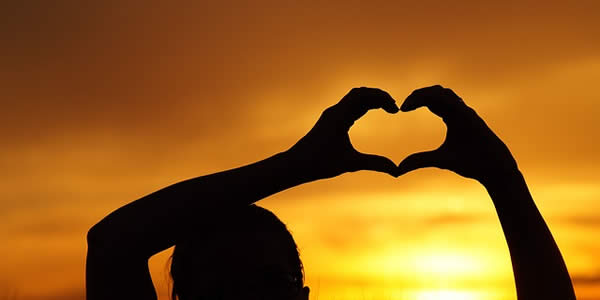 the silhouette of a person making their fingers construct the shape of a heart against the setting sun