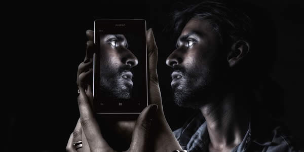 a man holds his cell phone reflecting his face
