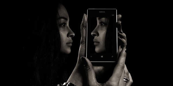a woman holding her cell phone reflecting her profile