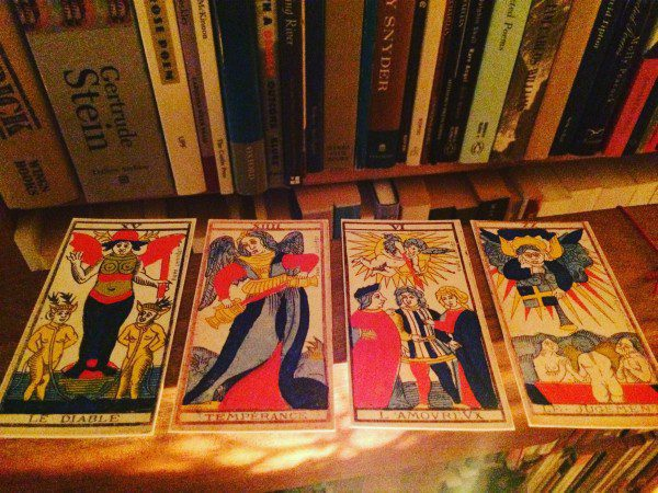 a photo of four tarot cards before books in the auhtor's library