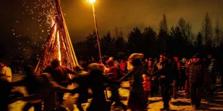 Kolyada revelers dancing around a bonfire