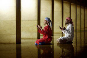 Two Muslim men praying