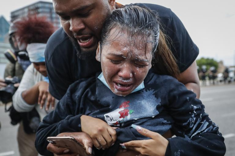 A protester reacts after being hit by pepper spray from police in Minneapolis