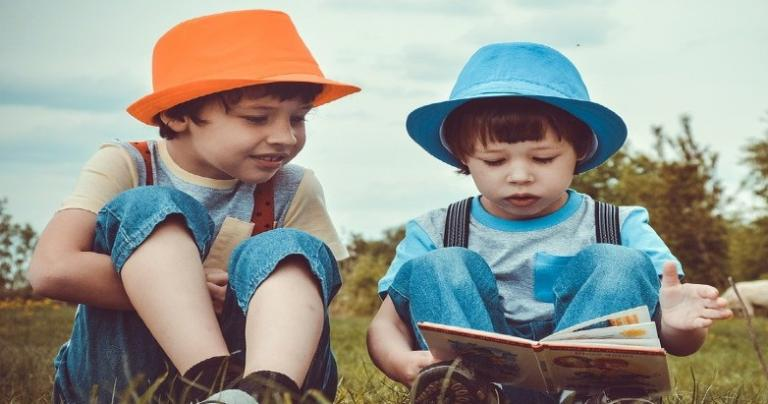 Two children in colorful fedoras read a book together.