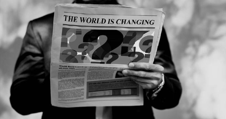 """A person holding a newspaper with a headline that reads """"The World Is Changing."""""""
