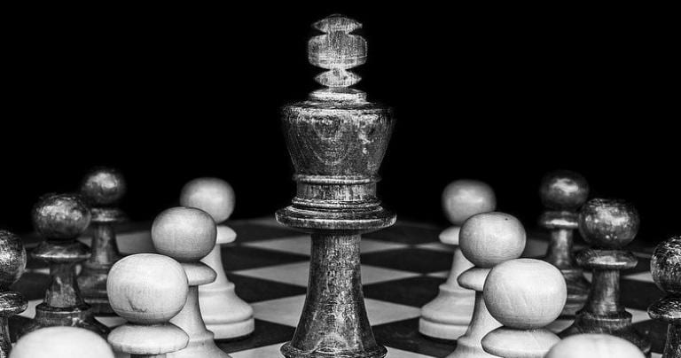A black and white photo of pawns surrounding a King chess piece.