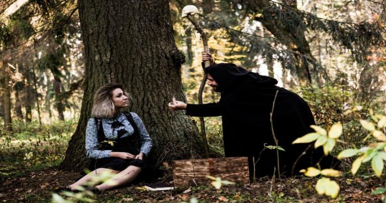 Woman sitting under a tree being visited by a stranger in a dark hooded robe and holding a staff.