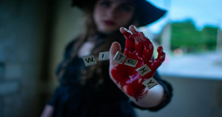 "A bloody hand in the foreground with Scrabble game pieces spelling out ""WITCHY."""