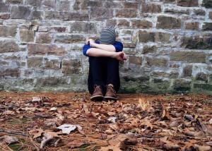 boy sitting on ground against brick wall