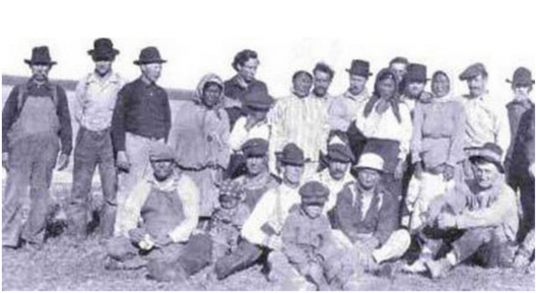 """My great grandmother is the small girl standing in front of her mother (third from right). My father's great-grandfather, """"Glass Eye Billy,"""" is seated second from left with an unidentified child on his lap. My father's great-great-grandmother is standing in the center in a striped shirt. The photo was taken circa 1924 near the mouth of the Igushik River on Bristol Bay.  (Info from McClatchydc.com)"""