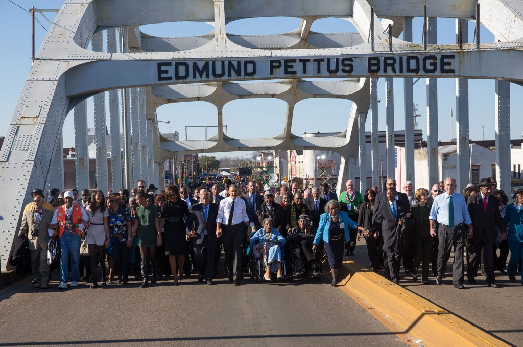 President Obama, former President George W. Bush, and Civil Rights Movement veterans and other commemoration attendees marching across the Edmund Pettus Bridge in March, 2015