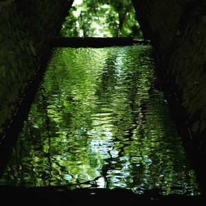 green and blue water in some kind of reservoir, surrounded by dark sides. the water is lit up by the reflection of trees.