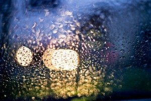 rain on the window of a car with yellow and purple light from the cars illuminating the droplets.