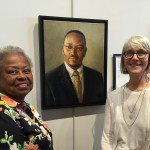 Dr. Maxine Smith with Prescott at Principle Gallery Charleston, with portrait of Reverend Pinckney
