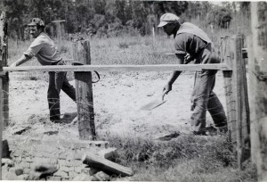 Two CPS workers covering an old privy hole at Camp 27 near Mulberry, FL
