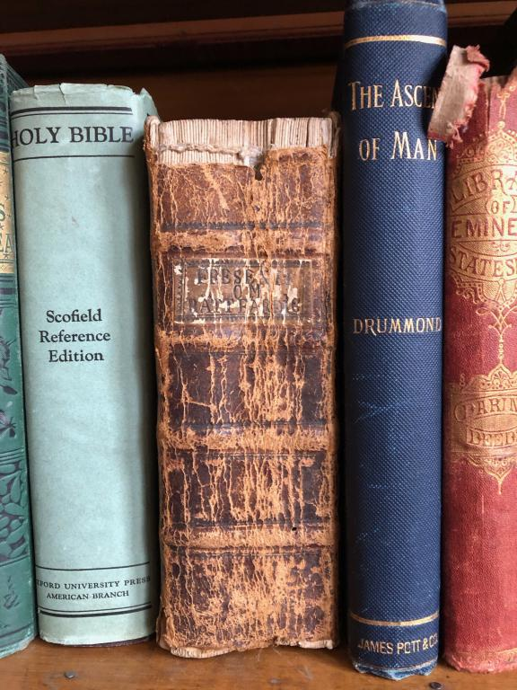 Three books in the Lindbergh library: a Scofield Bible, a Fresenius theology text, and Henry Drummond's Ascent of Man