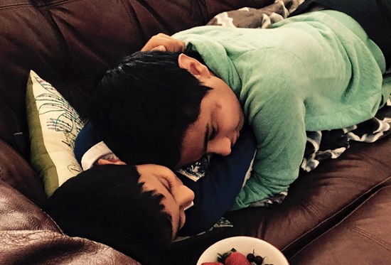 D lying on top of and hugging his little brother, H.