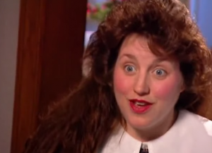 A screen cap from an early Duggar family special. Michelle is wearing a 'countenance-enhancing' big collar with her red sack-like jumper. Oh how much she's changed.