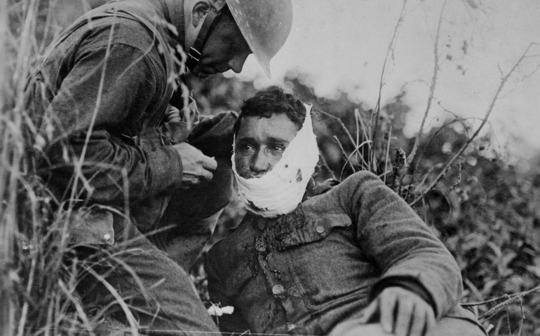 An American soldier wraps another soldier's head wound at Varennes-en-Argonne, France, in September 1918. (National Archives)