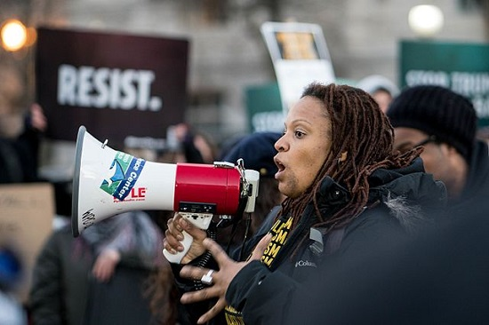 """By Lorie Shaull from Washington, United States - April Goggans of Black Lives Matter DC, Thursday evening rally against Trump's """"Muslim Ban"""" policies sponsored by Freedom Muslim American Women's Policy, CC BY-SA 2.0, https://commons.wikimedia.org/w/index.php?curid=55513766"""