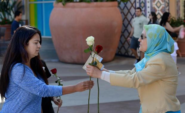 Fatemeh Nassirian, president of the Muslim Women Network of Southern California, hands out a free rose at the Irvine Spectrum on Saturday. ///ADDITIONAL INFORMATION: muslimroses.0412 Ð 4/11/15 Ð BILL ALKOFER, - ORANGE COUNTY REGISTER -