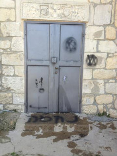 Graffiti on church door. Flammable liquid was likely to be used to scorch door as has happened in other attacks. Committee for the Uprooted Of Kafar Bir'em