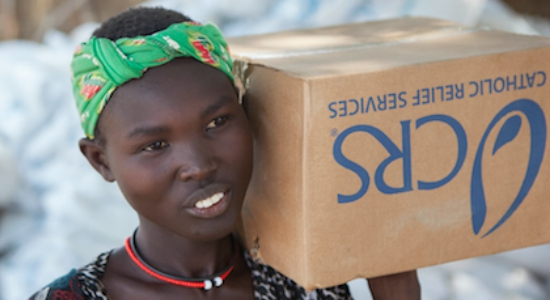 A girl receives a household items kit in Yolakot, South Sudan in Lake State. An estimated 716,100 have been displaced in South Sudan with an additional 166,900 fleeing to neighboring countries as a result of conflict that erupted in mid-December 2013. The Nile has become a lifeline for the people who have sought shelter along its shores. Catholic Relief Services and Caritas Internationalis have been responding with latrines, hand washing stations, and emergency shelter kits and non food items such as kitchen materials and hygiene materials. Image copyright Catholic Relief Services, used with permission