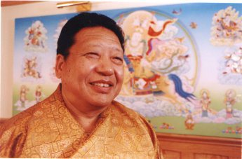 Dr Chöje Akong Tulku Rinpoche stands in front of a Tangka painting.