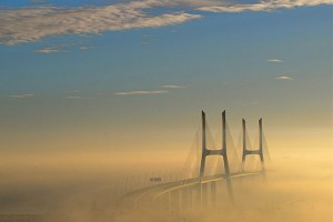 """Ponte Vasco da Gama 25"" by F Mira from Lisbon, Portugal - Merging in the mistUploaded by JotaCartas. Licensed under CC BY-SA 2.0 via Commons - https://commons.wikimedia.org/wiki/File:Ponte_Vasco_da_Gama_25.jpg#/media/File:Ponte_Vasco_da_Gama_25.jpg"