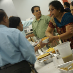 Kitchen volunteers keep trays of puri and papad flowing out to the hall.
