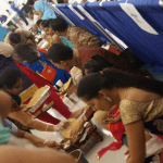 Volunteers squeeze between crowded rows to deliver food to those breaking their fast.