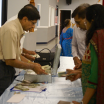 Guests exchange large bills at the entry table in order to offer small financial gifts to those who have fasted.