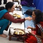 Jain educator Darshana Shah offers a celebratory spoonful to a friend and fast-breaker.