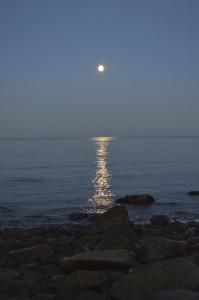 Full moon over the ocean and a rocky beach