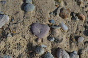 A heart-shaped stone in the sand at a beach