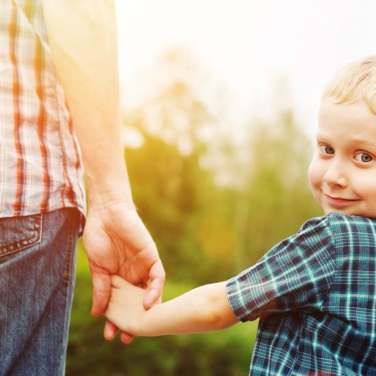 boy holding dad hand