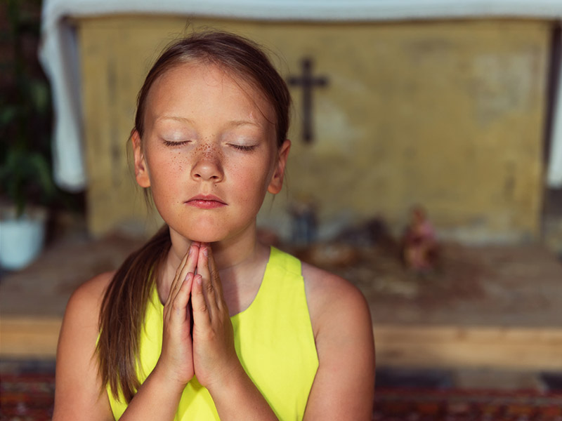 girl-praying-at-church_credit_shutterstock.com