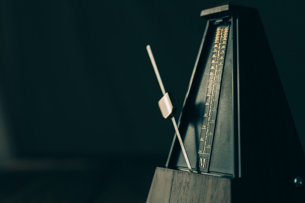 Color shot of a vintage metronome, on a black background.