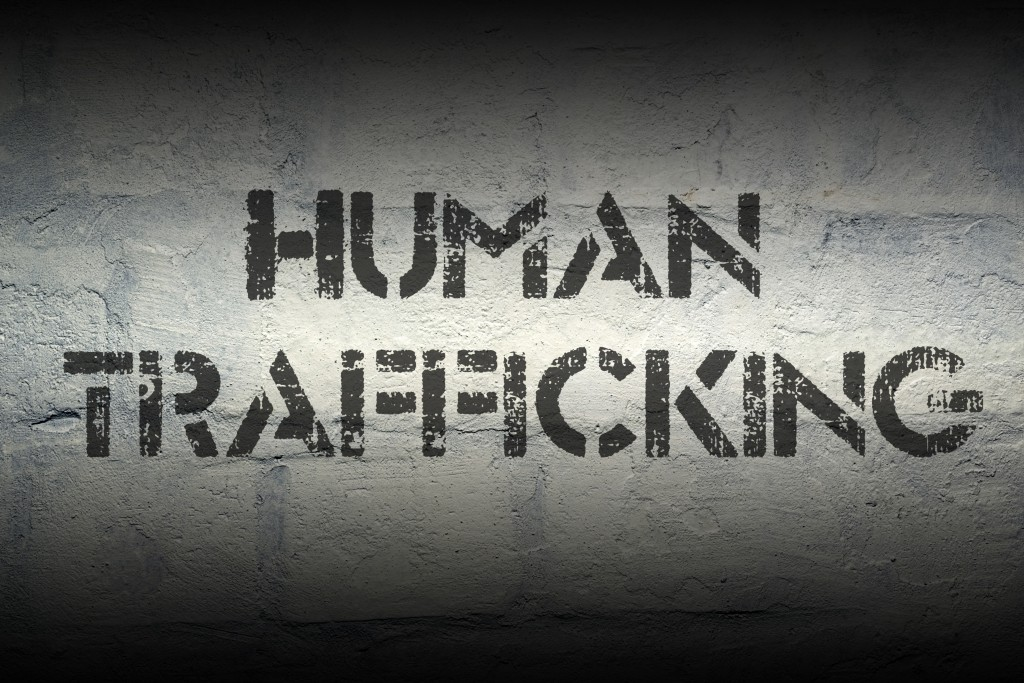human trafficking stencil print on the grunge white brick wall