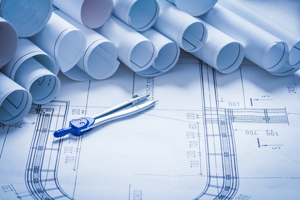 Pair of compasses with blueprint rolls building and architecture concept