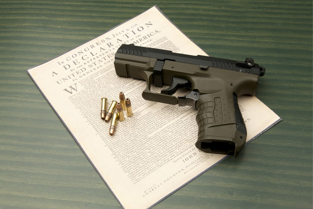 A close up of a hand gun with bullets resting on the Declaration of Independence.
