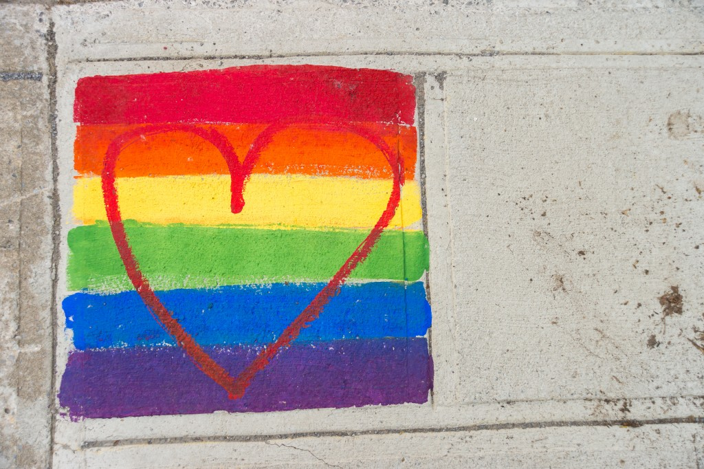 Gay rainbow flag and red heart painted on a sidewalk