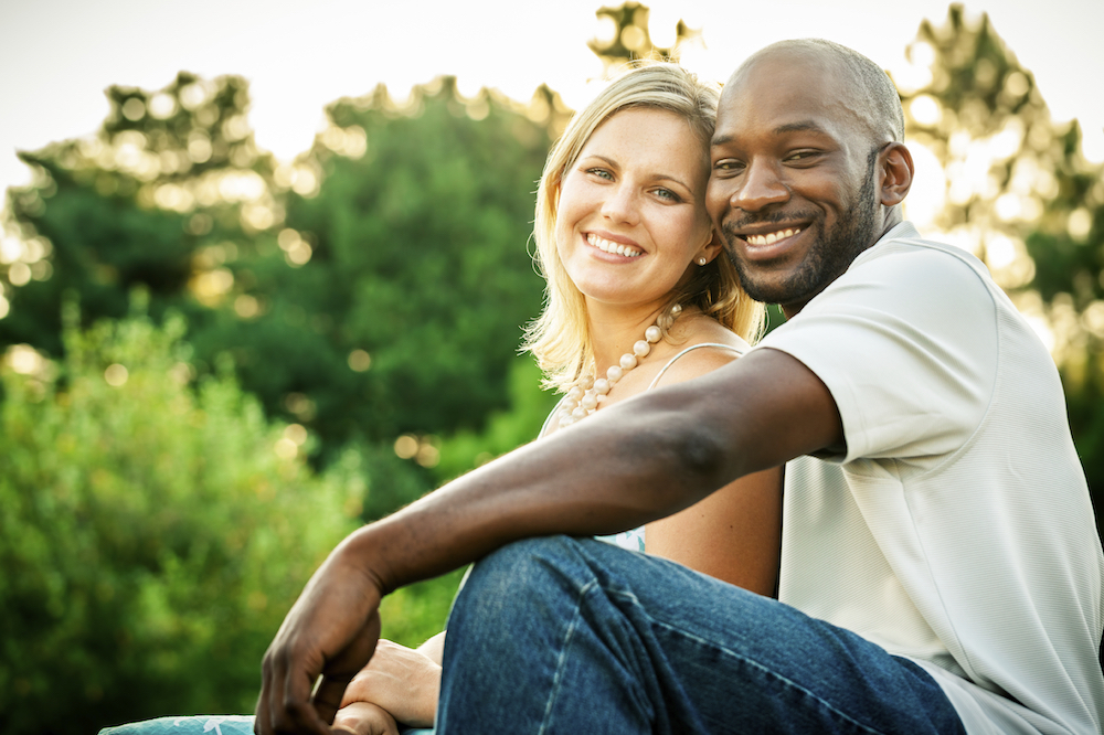 Beautiful mixed race couple or friends sitting at a park in the summer