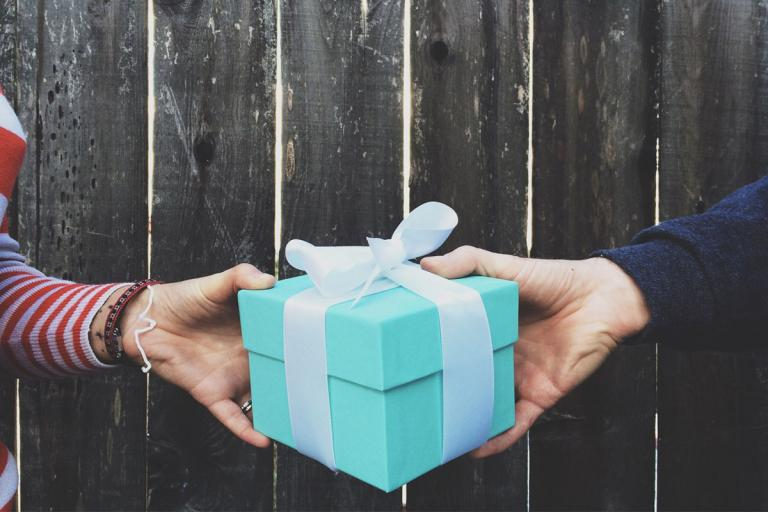 Woman and man exchanging a wrapped gift