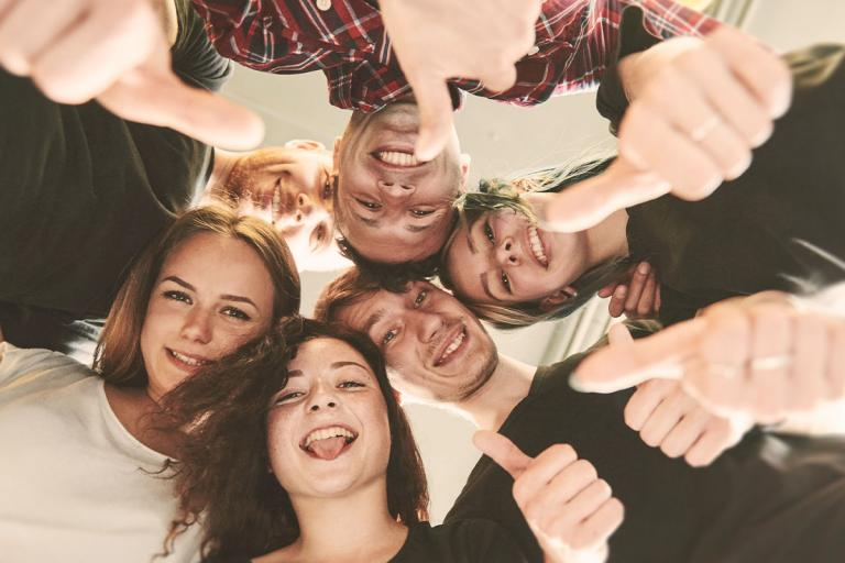 group of smiling teenagers in a circle