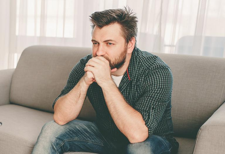 Frustrated man on sofa - When You Tease Your Husband, It's Really No Joke