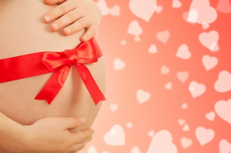concept, a symbol of procreation. pregnant belly  of woman with red ribbon