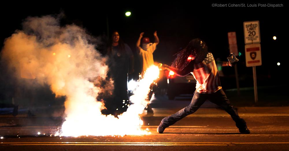 Protestor Throws Tear Gas Canister Back at Police  - photo by Robert Cohen, St. Louis Post-Dispatch